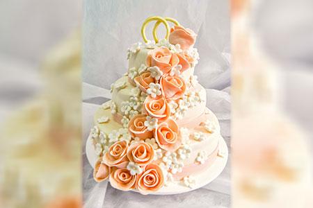 Бело-кремовый свадебный торт с розочками персикового цевта