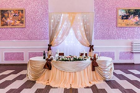 Текстильное форрмление стола молодоженов и стены позади в бежево-коричневом цвете