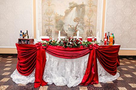 Оформление стол молодоженов бело-красной тканью и кружевом