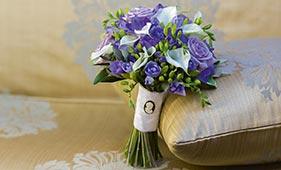 Свадебный букет невесты из сиреневых роз и фрезий и белых калл