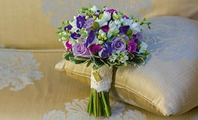 Свадебный букет невесты из сиреневых роз бело-фиолетовых лизиантусов и белых фрезий