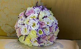 Бело-сиреневый свадебный букет невесты из роз лизиантусов и фрезий