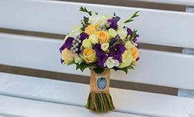Кремово-фиолетовый свадебный букет невесты из роз и лизиантусов