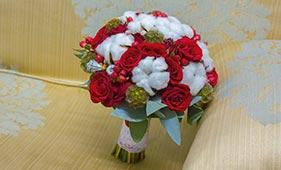 Свадебный букет невесты из красных роз и белого хлопка