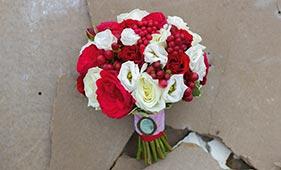 Бело-красный букет невесты из роз лизиантусов и красных ягод