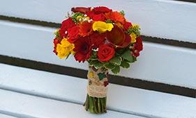 Красно-желтый свадебный букет невесты из роз и калл