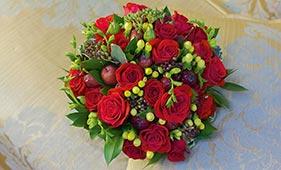Красно-зеленый свадебный букет невесты из роз с зелеными ягодами