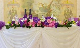 Свадебная цветочная композиция на стол молодоженов из фиолетовых орхидей и розовых роз