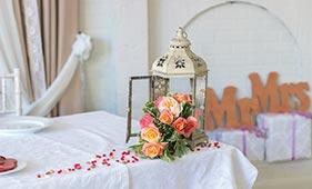 Свадебная цветочная композиция на стол молодоженов из коралловых пионовидных роз в фонариках