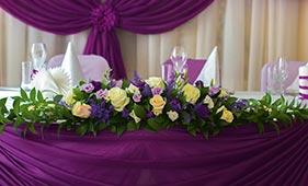 Свадебная цветочная композиция на стол молодоженов из белых роз и фиолетовых лизиантусов