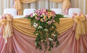 Свадебная цветочная композиция на стол молодоженов из кремовых и розовых роз