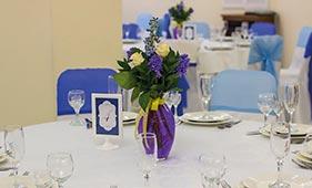Бело-фиолетовая Свадебная цветочная композиция на стол гостей из роз и маттиолы в стеклянной вазе