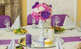 Бело-розово-фиолетовая Свадебная цветочная композиция на стол гостей из роз орхидей и гортензий на подсвечнике