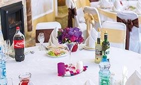Свадебная цветочная композиция на стол гостей из фиолетовых орхидей и розовых роз в мартинке