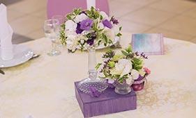 Свадебная цветочная композиция на стол гостей из белых гортензий и сиреневых лизиантусов в мартинке