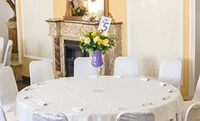 Свадебная цветочная композиция на стол гостей из желтых и белых роз в высокой вазе