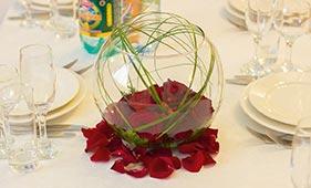 Свадебная цветочная композиция на стол гостей из красных роз в круглой стеклянной вазе