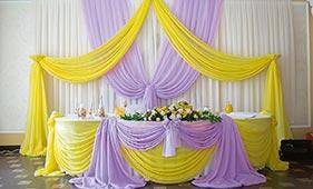 Желто-сиреневое текстильное оформление стола молодоженов